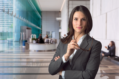 Businesswoman holding her glasses standing in lobby of office.